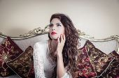 picture of mystique  - Pretty model girl wearing white dress sitting on victorian sofa with thoughtful facial expression - JPG