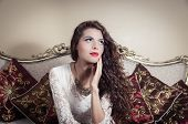 picture of bolivar  - Pretty model girl wearing white dress sitting on victorian sofa touching her face and thoughtful expression - JPG