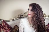 picture of mystique  - Pretty model girl wearing white dress sitting on victorian sofa posing for camera looking to the side - JPG