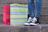 stock photo of street-walker  - Female feet in gumshoes near shopping bag on  stone stairs - JPG