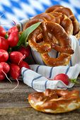 stock photo of pretzels  - Fresh Bavarian pretzels in a breadbasket and a bunch of red radishes on a wooden table - JPG