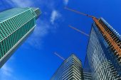 stock photo of high-rise  - Uncompleted high-rise buildings with cranes against blue sky. ** Note: Visible grain at 100%, best at smaller sizes - JPG