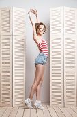 image of jalousie  - Young beautiful woman wearing shorts and  stripy top posing in front of a jalousie - JPG