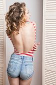 stock photo of jalousie  - Young beautiful woman wearing jeans shorts and  top posing in front of a jalousie - JPG
