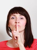 stock photo of silence  - Woman showing hand silence sign holding index finger to lips - JPG