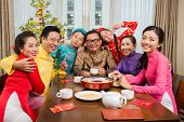 stock photo of national costume  - Portrait of Vietnamese family in national costumes gathered at the Tet table - JPG