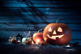 stock photo of scary haunted  - Halloween pumpkin head jack lantern on wooden background - JPG