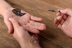 foto of mehndi  - Process of applying Mehndi on female hand close up - JPG