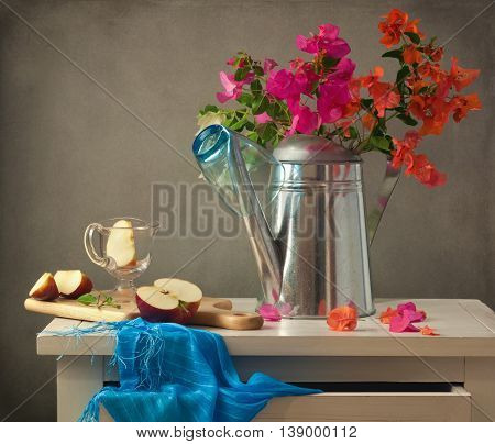 Still life with flowers and apple on wooden white table over grunge background