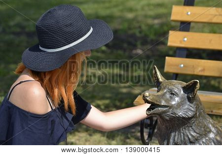 Summer red-haired girl in a black hat and a black tank top carefully considering fox public monument on the background of the bench