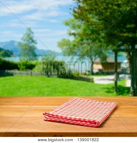 Empty wooden table with checked tablecloth over beautiful landscape. Perfect for product montage.