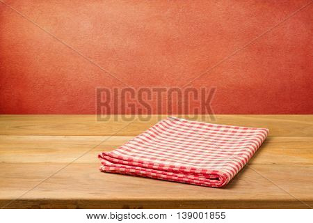 Empty wooden table with checked tablecloth over grunge red concrete wall. Ready for product montage