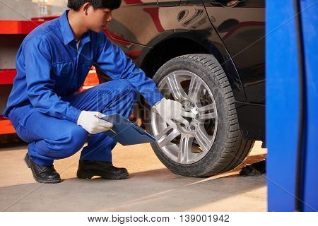 Young Vietnamese auto mechanic checking tyre in garage