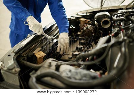 Cropped image of auto mechanic checking car engine