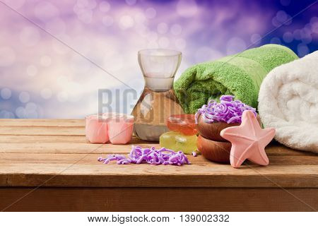 Spa setting with soap and towels on wooden table over dreamy bokeh background