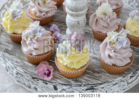 Purple And Yellow Cupcakes With Sugared Edible Flowers On Vintage Cake Stand.