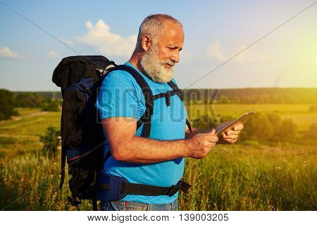 Sporty aged man with rucksack behind his back is standing in the field and looking something up in his data tablet