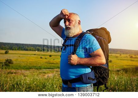 Fit aged man in casual clothes with rucksack behind his back is standing in the middle of the field wiping his forehead
