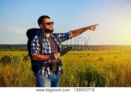 Healthy bearded adult in sunglasses with rucksack behind his back is holding a data tablet and pointing at something in the distance in the field