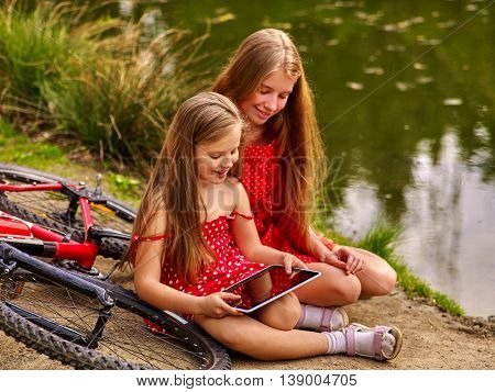Bikes cycling girl. Girl wearing red polka dots dress recreation near bicycle into park. Children watch tablet pc. Girl in ecotourism.
