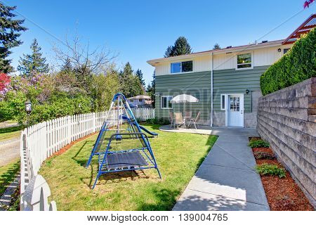 House Exterior. Fenced Back Yard With Patio Area And Kids Playground