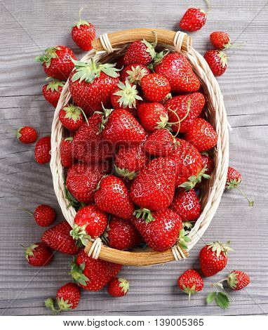 Sweet strawberries in basket on wooden table. Close up top view high resolution product