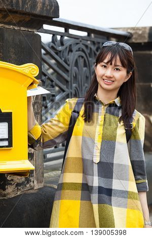 Young smiling asian woman with check pattern shirt stand beside a nostalgic yellow mailbox and put a post card inside