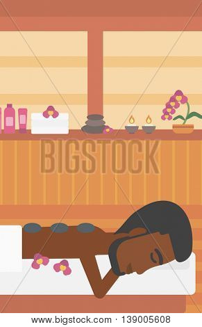 An african-american man relaxing while getting stone therapy massage in the spa center. Man having back massage in spa salon. Vector flat design illustration. Vertical layout.