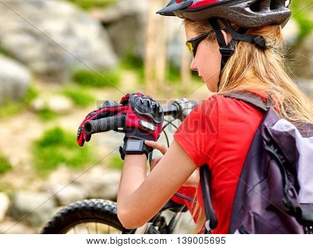 Portrait of bikes bicyclist girl. Bicyclist girl watch on smart watch. Girl looking for road. Smart watch best assistant in travel. Stones on background. Back view.