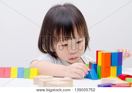 little Asian girl playing colorful wood blocks
