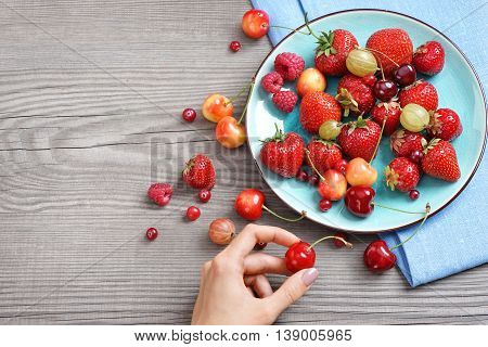 Ceramic plate with cherries strawberries and raspberries at old wooden table. Close up high resolution product. Harvest Concept