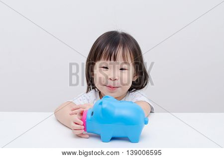 Little Asian girl smiling with her piggy bank