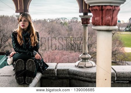 Girl Sitting On Edge Of Belvedere Castle At Central Park In Manhattan, New York City