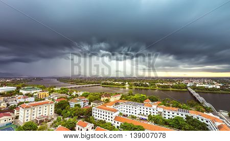 Hue, Vietnam - June 21st, 2015: City in the afternoon with billowing clouds when storm comes, below  ancient red tile house as urban areas along river beautiful and idyllic in Hue, Vietnam