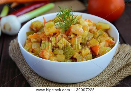 Vegetarian ragout of summer vegetables (zucchini carrots tomatoes spices garlic chilli) in a white bowl on a wooden background. Dietary dish.
