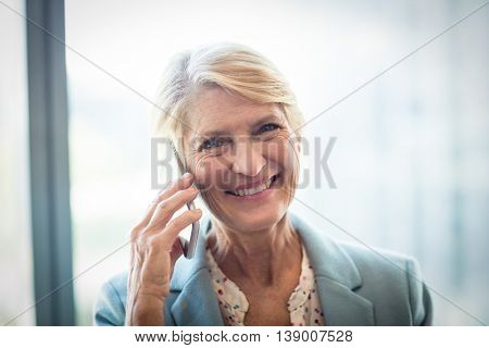 Portrait of woman talking on mobile phone in the office