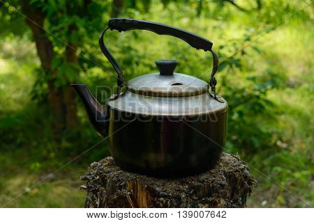 Vintage kettle for heating water on an old stump in the background of nature. Men's style