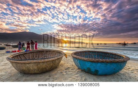 Da Nang, Vietnam, June 26, 2015: Sunrise over seaside with sunlight to create stars and double pannier foreground boat, people exercising and watching fishermen bring fish on sale in Da Nang, Vietnam