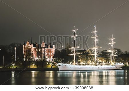 Red Castle And A Boat At Night In Stockholm, Sweden
