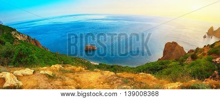 Dramatic sunset at cape fiolent with rocks and grass at foreground. Panoramic view. Crimea