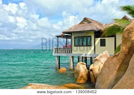 Close thatched roof bungalow on island with a house located on bay floor where resort rocky honeymoon for newly married couple, beautiful and idyllic