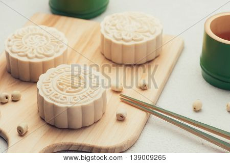 Retro vintage style Chinese mid autumn festival foods. Traditional mooncakes on table setting
