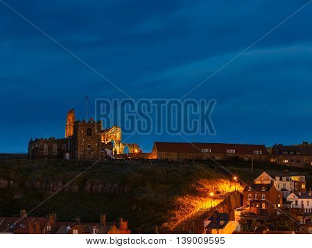 WHITBY ENGLAND - JULY 16: Whitby Abbey atop the cliffs at night. In Whitby North Yorkshire England. On 16th July 2016.