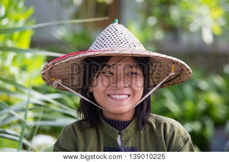 NGAPALI MYANMAR - JANUARY 23 2016: Portrait burmese girl a straw hat in local market. Myanmar Burma