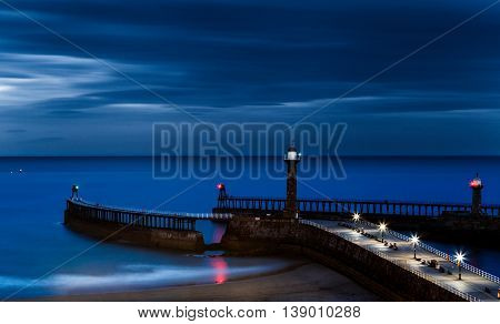 WHITBY ENGLAND - JULY 16: The West Lighthouse and pier at night. Long exposure. In Whitby North Yorkshire England. On 16th July 2016.