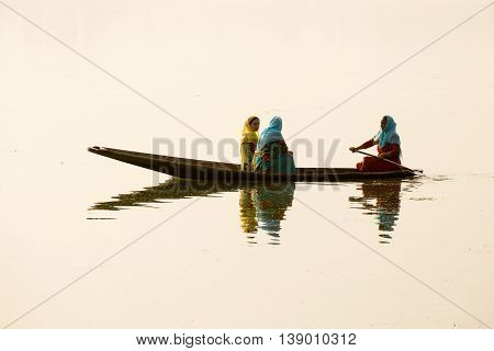SRINAGAR INDIA - JULY 07 2015 : Lifestyle in Dal lake local people use Shikara a small boat for transportation in the lake of Srinagar Jammu and Kashmir state India