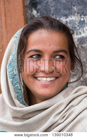 LEH INDIA - JUNE 24 2015: Unknown smiling poor girl begs for money from a passerby on the street in Leh Ladakh. Poverty is a major issue in India