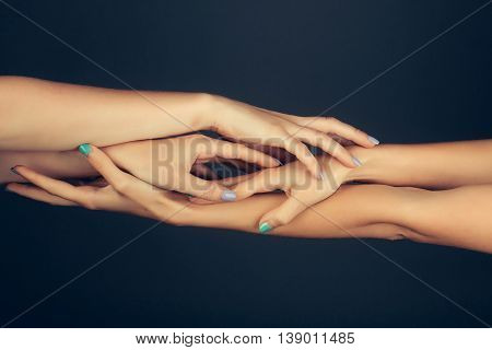 four female hands with soft tender skin and blue manicure holding and touching each other making massage on grey background