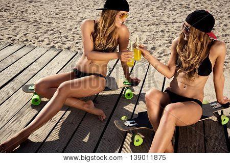 female twins having fun in the sun sitting on a skateboard.