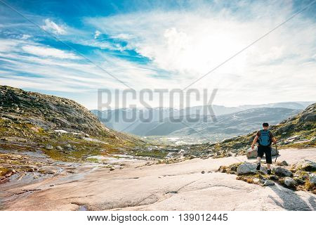 Young Man Goes On A Mountain Hiking Trail In The Mountains Of Norway. Landscape Of Norwegian Mountains. Nature Of Norway. Travel And Hiking. Amazing Scenic View At Sunny Summer Day. Scandinavia. Blue Sky
